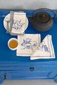 Teekanne, Teeschälchen & mit verschiedenen Motiven bestickte Leinenservietten auf blauer Kommode
