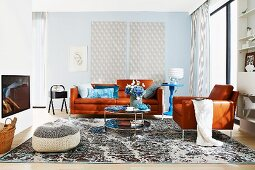 Klassisches Wohnzimmer mit braunem Ledersofa und blauen Accessoires