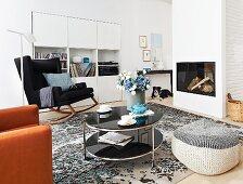 Wohnzimmer mit weissem Schrankregal, Schaukelstuhl, Kamin, Beistelltisch und Sitzsack