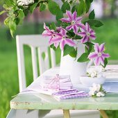 Vase of clematis flowers and dish of apple blossom on garden table