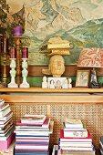 Collection of objet d'art on narrow shelf below painting of mountain landscape