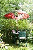 Seating area in summery garden with garden chair, garden table & red Thai-style parasol