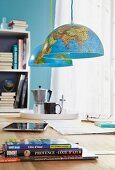Two halves of a globe as pendant lamps hanging over a table