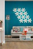Wohnbereich mit Sofa, Stehlampe & moderner Wandleuchte vor blauer Wand
