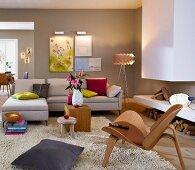 Wohnzimmer mit Sofa, Holzstuhl & Kamin