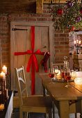 A wooden door decorated with a bow and a stocking with a sprig of mistletoe hung with Christmas decorations above a table in the foreground