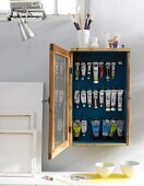 Canvases and a wooden wall cupboard for storing paint tubes