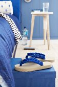 Blue-and-white flip-flops with crocheted straps in front of bed with blue bedclothes
