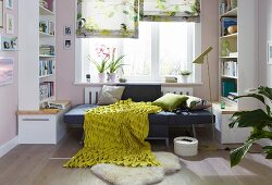 An armchair folded out into a bed with cushions and a green-and-yellow structured blanket between bookshelves