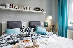 A bookshelf above a double bed with cushions and a breakfast tray