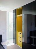 Dressing room with black, high gloss, sliding doors in front of a yellow cabinet unit