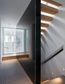 Black, high-gloss stairwell and wall with recessed spotlights above the stairs