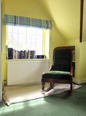 A green upholstered rocking chair in reading corner by a window