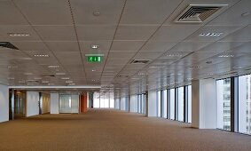 Ceiling panels with technical installations in spacious hall with floor-to-ceiling windows
