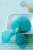 A turquoise Easter egg with a lace bow