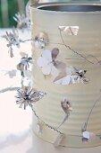 Konservendose, mit Draht und Silberblumen umwickelt