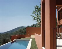 Sun above a pool in a garden and Mediterranean home with a reddish brown facade
