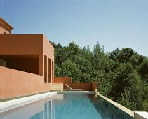 Vacation mood - by the pool in front of a Mediterranean home with a reddish brown facade