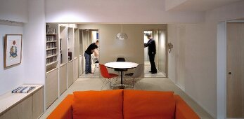 Orange sofa and bistro table with chair in Bauhaus style between two open hallways