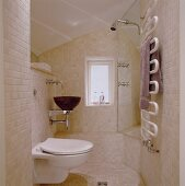 Bathroom tiled with light colored tiles and WC beside a vanity with a wood wash basin across from a shower stall