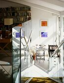 Descending stairs with a glass balustrade and view of a writing desk in an open room