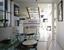 Tableware on a glass top dining table in an open, modern living room with stairs