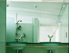 Designer bath with glass wash basins and designer fittings in front of a mirrored wall