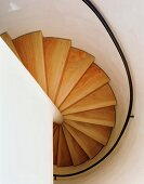 View of a curved stairway with wooden steps and black hand rail in an enclosed stairwll