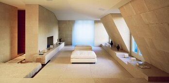 Minimalist living room under a roof with ottomans upholstered in white and stone tiles on the wall and floor