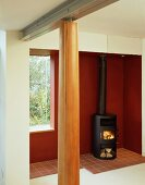 Wood burning stove in front of a red wall and wooden columns in a lobby