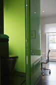 A view into a bathroom with a toilet against a green glass wall