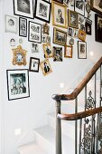 A traditional stairwell with a collection of photos in various frames