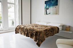 A brown furry blanket on a double bed in a minimalistic bedroom