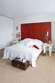 White bedroom with red screen as a head board