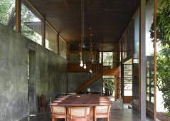 Dining table and traditional chairs with rattan backs in contemporary concrete living space next to ceiling-height terrace doors