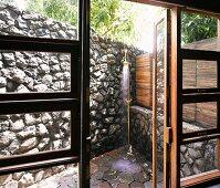 View through open terrace door of vintage brass outdoor shower in corner by stone wall