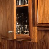 Detail of a fitted walnut cupboard with an open door an a glimpse of glasses