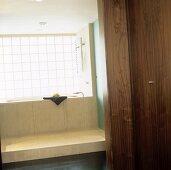 A view through an open door onto a bath tub and a light wooden pedestal