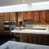 An open-plan fitted kitchen with wooden cupboards and a bar with a white surface
