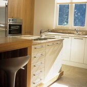A free-standing sink with white cupboards underneath and a wooden counter in a contemporary kitchen