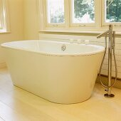 A white free-standing bath tub with a designer floor tap on light wooden floor boards