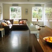 A walnut kitchen counter with a stainless steel bracket with a comfortable sofa in front of a window