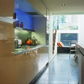 A modern fitted kitchen with shiny cupboards and coloured lights behind a glass wall