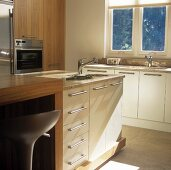 A fitted kitchen with an island counter and a sink under the window
