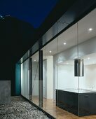 Evening on a terrace with a gravel floor and a view into an illuminated, open-plan, designer kitchen