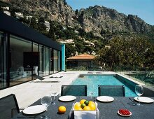 A contemporary house with a view of a rocky landscape with a table laid on a terrace in front of a pool