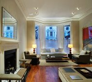 Classic living room with fireplace and light-grey sofa set in bay window