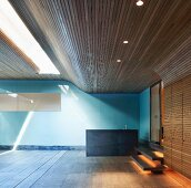 Modern room with wood cladding on ceiling and wall and covered swimming pool