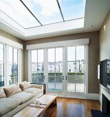 Light sofa and wooden coffee table under glass ceiling and next to terrace doors