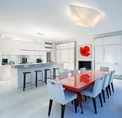 Open-plan dining room with red painted dining table and white upholstered chairs in front of kitchen counter and bar stools
